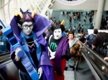Drew Husted (left) dressed as Eridan and Natalie Christie (right) dressed as Kanaya make their way up an escalator to the second floor of Comic-Con.